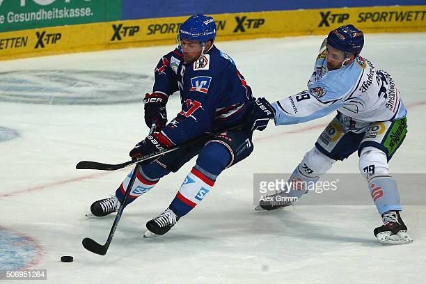 Marcus Kink of Mannheim is challenged by Blaine Down of Straubing during the DEL match between Adler Mannheim and Straubing Tigers at SAP Arena on...