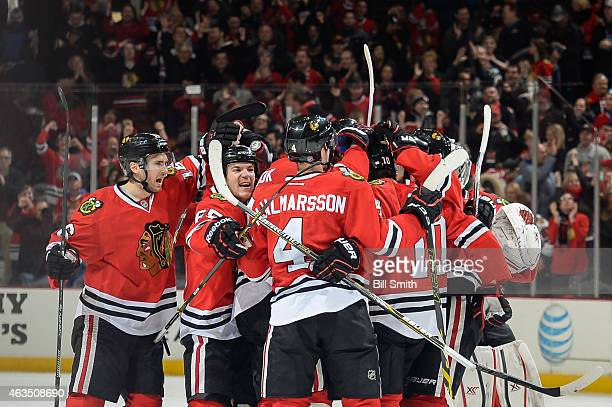 Marcus Kruger and Andrew Shaw of the Chicago Blackhawks celebrate with the team after defeating the Pittsburgh Penguins 2-1 during the NHL game at...