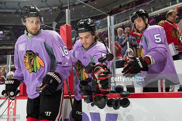 Marcus Kruger Andrew Shaw and David Rundblad of the Chicago Blackhawks wear purple jerseys in honor of 'Hockey Fights Cancer' night during warmups...