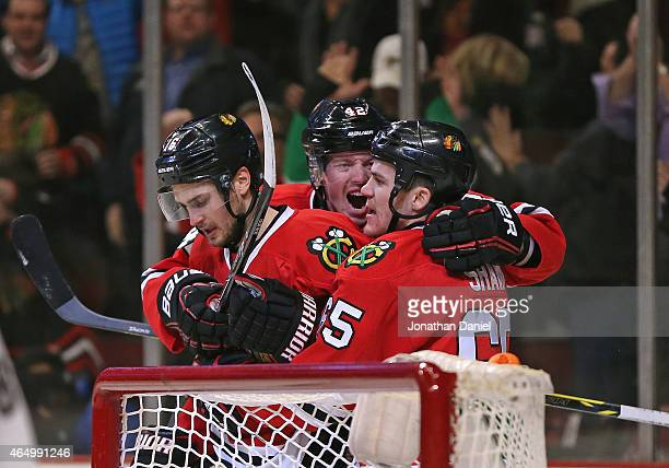 Marcus Kruger Joakim Nordstrom and Andrew Shaw of the Chicago Blackhawks celebrate Kruger's second period goal against the Carolina Hurricanes at the...