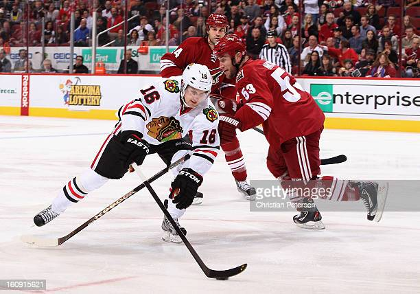 Marcus Kruger of the Chicago Blackhawks attempts to skate around Derek Morris of the Phoenix Coyotes during the first period of the NHL game at...