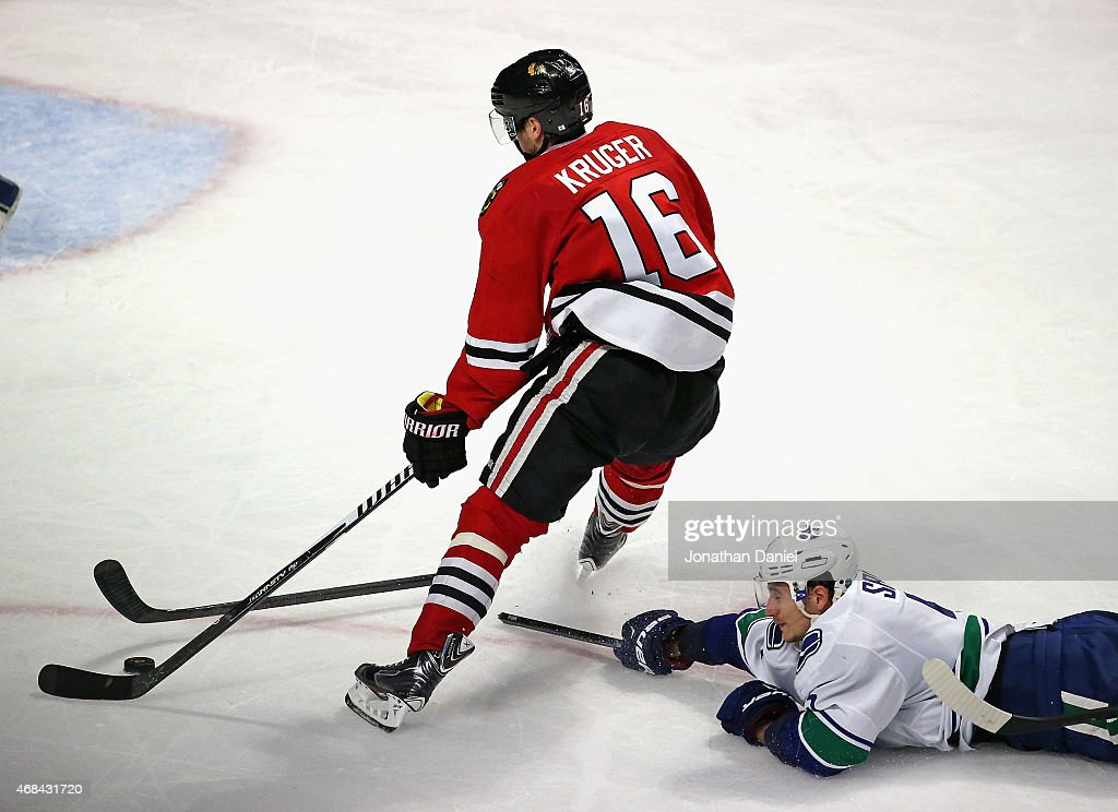 Marcus Kruger #16 of the Chicago Blackhawks breaks the stick of Luca Sbisa #5 of the Vancouver Canucks on his way to scoring a third period goal at the United Center on April 2, 2015 in Chicago, Illinois. The Blackhawks defeated the Canucks 3-1.