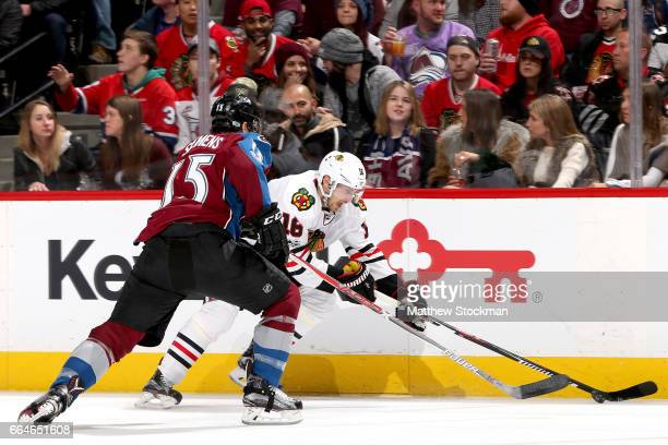 Marcus Kruger of the Chicago Blackhawks brings the puck down along the boards against Duncan Siemens of the Colorado Avalanche at the Pepsi Center on...