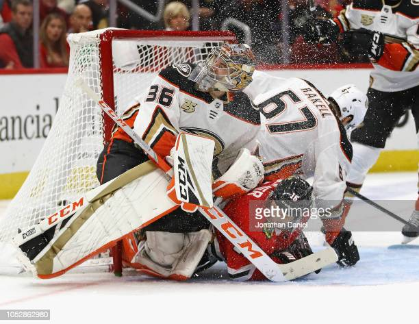 Marcus Kruger of the Chicago Blackhawks colllides with John Gibson and Rickard Rakell of the Anaheim Ducks at the United Center on October23 2018 in...
