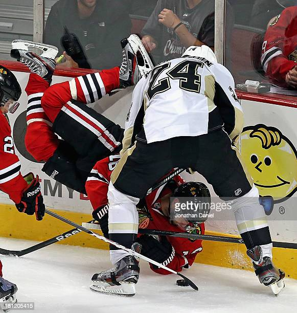 Marcus Kruger of the Chicago Blackhawks flips in the air while battling for the puck with Brendan Mikkelson of the Pittsburgh Penguins during an...