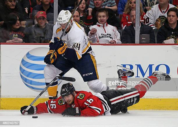 Marcus Kruger of the Chicago Blackhawks hits the ice as he battles for the puck with Victor Bartley of the Nashville Predators at the United Center...
