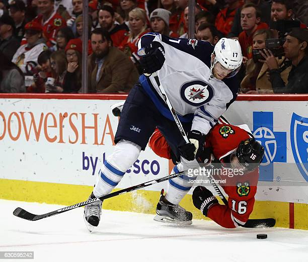 Marcus Kruger of the Chicago Blackhawks hits the ice while battling for the puck with Adam Lowry of the Winnipeg Jets at the United Center on...