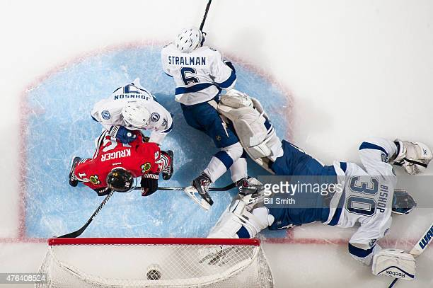 Marcus Kruger of the Chicago Blackhawks is pushed by Tyler Johnson of the Tampa Bay Lightning as goalie Ben Bishop lays on the ice during Game Three...