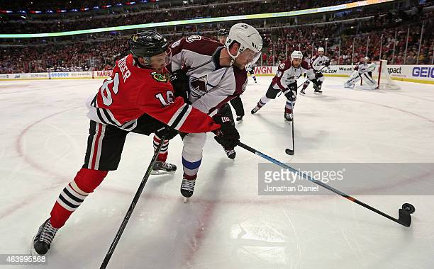 Marcus Kruger of the Chicago Blackhawks knocks the puck away from Jan Hejda of the Colorado Avalanche at the United Center on February 20 2015 in...