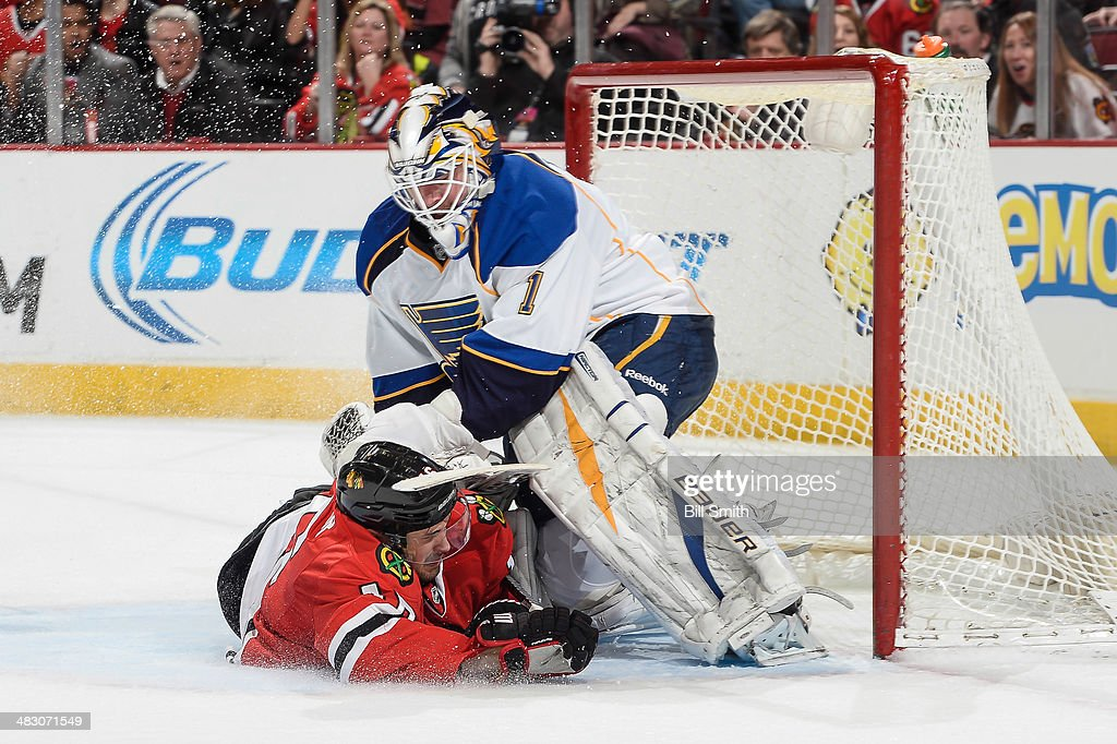 Marcus Kruger #16 of the Chicago Blackhawks slides into goalie Brian Elliott #1 of the St. Louis Blues during the NHL game on April 06, 2014 at the United Center in Chicago, Illinois.