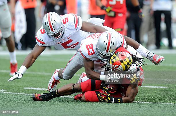 Marcus Leak of the Maryland Terrapins is tackled by Tyvis Powell and Raekwon McMillan of the Ohio State Buckeyes at Byrd Stadium on October 4 2014 in...