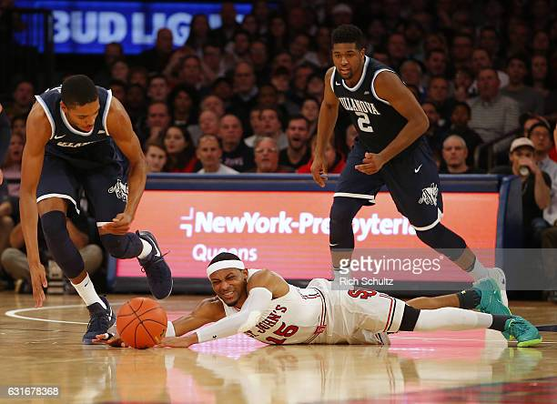 Marcus LoVett of the St John's Red Storm dives for a loose ball as Mikal Bridges and Kris Jenkins of the Villanova Wildcats chase during the first...