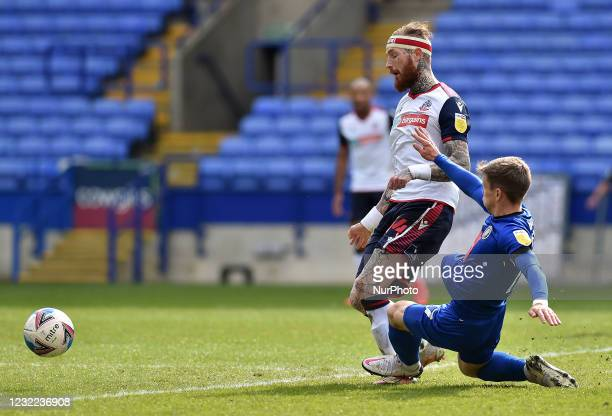Marcus Maddison of Bolton Wanderers is tackled by Lloyd Kerry of Harrogate Town during the Sky Bet League 2 match between Bolton Wanderers and...