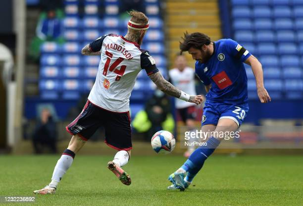 Marcus Maddison of Bolton Wanderers tussles with Connor Hall of Harrogate Town during the Sky Bet League 2 match between Bolton Wanderers and...