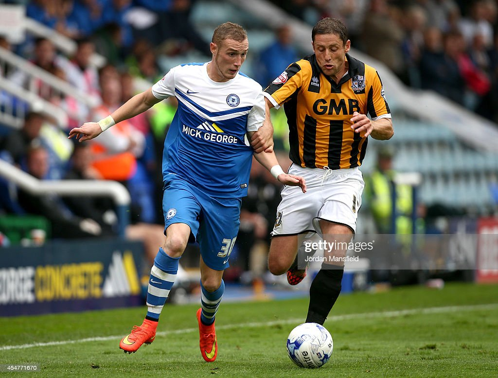 Marcus Maddison of Peterborough takes the ball past Michael Brown of Port Vale during the Sky Bet League One match between Peterborough United and Port Vale at London Road Stadium on September 6, 2014 in Peterborough, England.