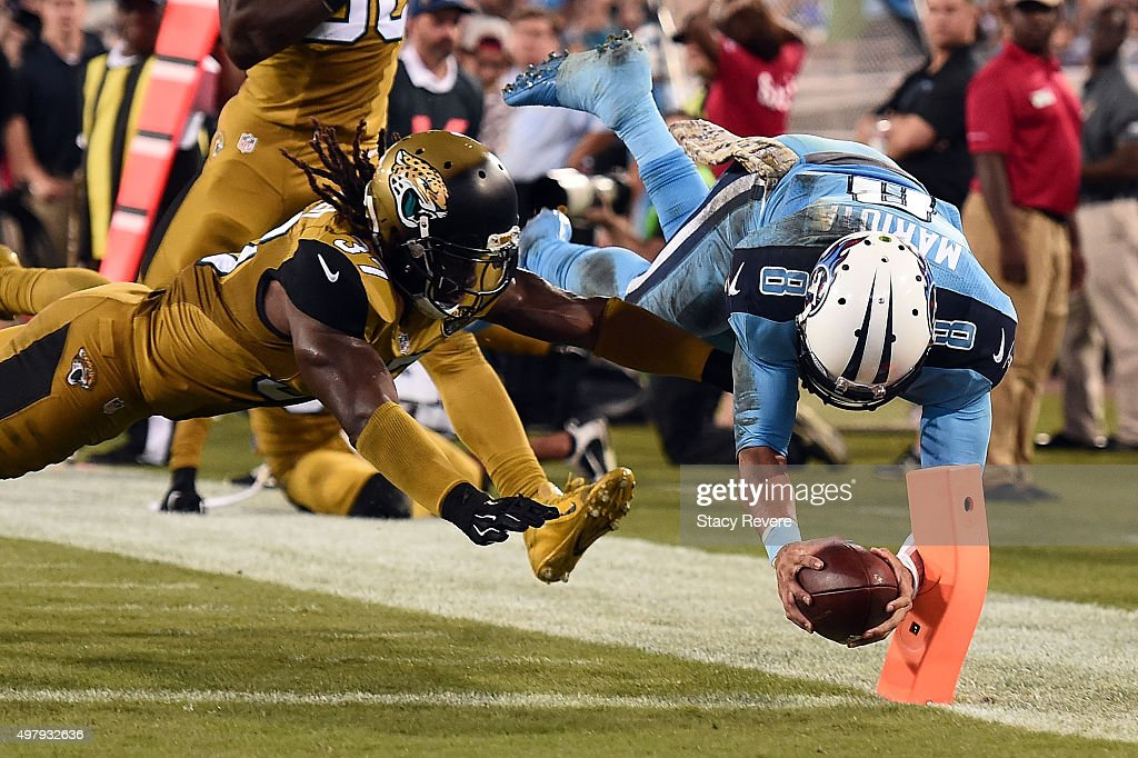 Marcus Mariota #8 of the Tennessee Titans dives for touchdown in front of Johnathan Cyprien #37 of the Jacksonville Jaguars during the third quarter of a game at EverBank Field on November 19, 2015 in Jacksonville, Florida.