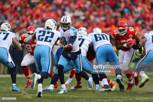 Marcus Mariota of the Tennessee Titans hands the ball off against the Kansas City Chiefs during the AFC Wild Card playoff game at Arrowhead Stadium...