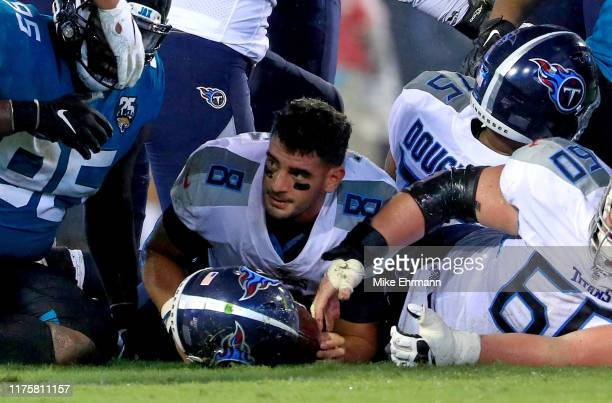 Marcus Mariota of the Tennessee Titans has his helmet knocked off after being tackled during a game against the Jacksonville Jaguars at TIAA Bank...