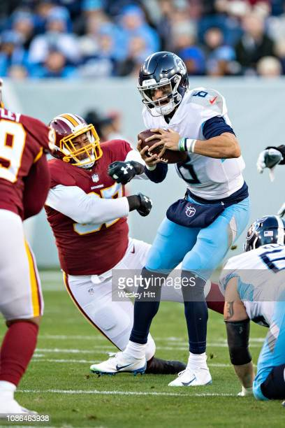 Marcus Mariota of the Tennessee Titans is hit in the backfield by Tim Settle of the Washington Redskins at Nissan Stadium on December 22 2018 in...