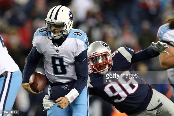 Marcus Mariota of the Tennessee Titans is tackled by Geneo Grissom of the New England Patriots during the fourth quarter in the AFC Divisional...