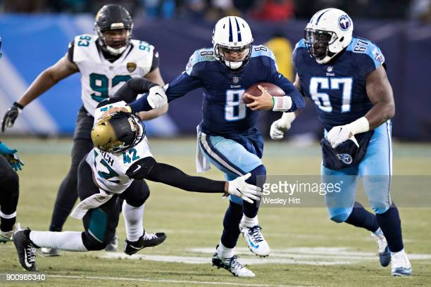 Marcus Mariota of the Tennessee Titans runs the ball and stiff arms Barry Church of the Jacksonville Jaguars at Nissan Stadium on December 31 2017 in...