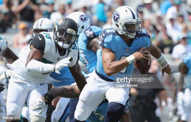 Marcus Mariota of the Tennessee Titans runs with the football in front of Dante Fowler of the Jacksonville Jaguars during the first half of their...