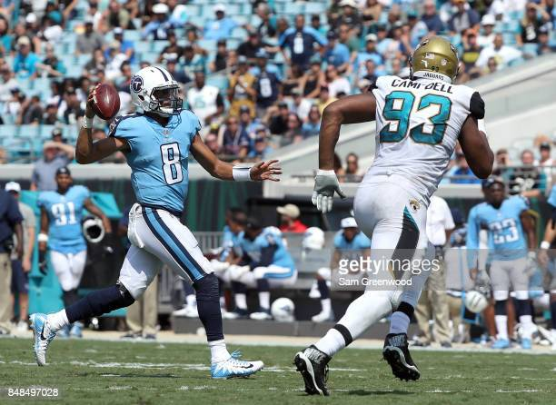 Marcus Mariota of the Tennessee Titans runs with the football in front of Calais Campbell of the Jacksonville Jaguars during the second half of their...