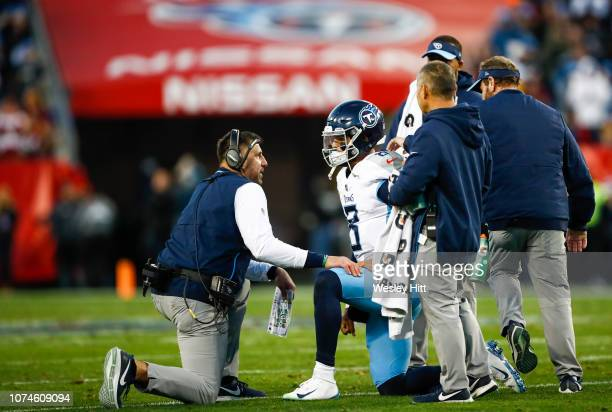 Marcus Mariota of the Tennessee Titans talks to head coach Mike Vrabel after being tackled during the second quarter against the Washington Redskins...