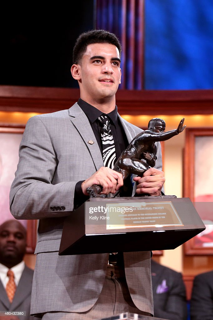 Marcus Mariota, quarterback for the University of Oregon Ducks, hoist the trophy after being named the 80th Heisman Memorial Trophy Award winner during the 2014 Heisman Trophy Presentation at the Best Buy Theater on December 13, 2014 in New York City.