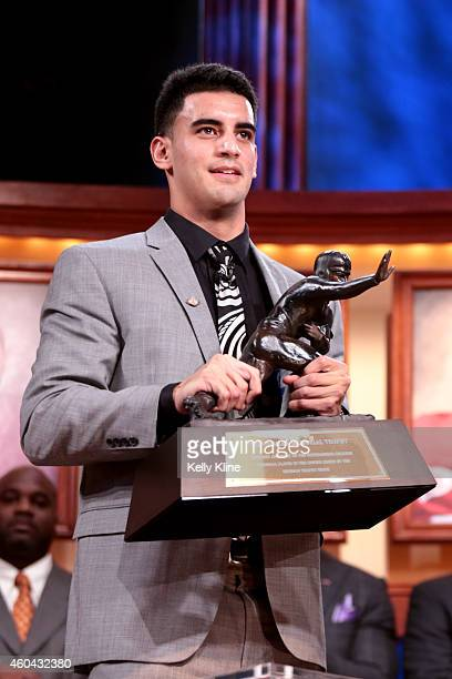 Marcus Mariota quarterback for the University of Oregon Ducks hoist the trophy after being named the 80th Heisman Memorial Trophy Award winner during...