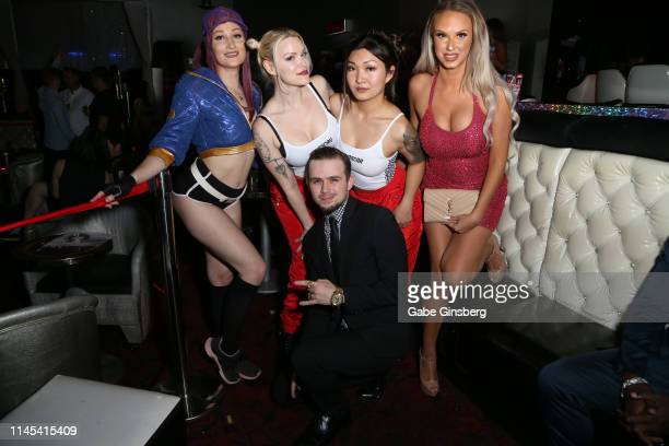 Marcus Maze Franklin poses with cosplay models Holly Wolf Dangrrr Doll Gaius Cosplay and Eden Victoria during Larry Flynt's Hustler Club The Gamer...