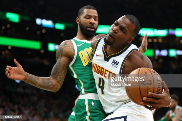 Marcus Morris of the Boston Celtics defends Paul Millsap of the Denver Nuggets during the first quarter at TD Garden on March 18 2019 in Boston...