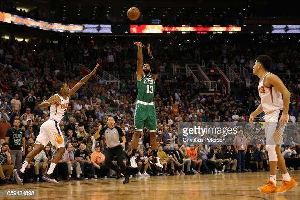 Marcus Morris of the Boston Celtics hits a game tying threepoint shot over Trevor Ariza of the Phoenix Suns during the final moments of the second...