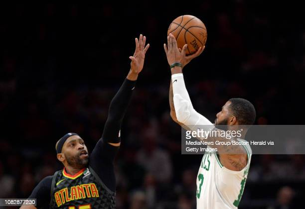 Marcus Morris of the Boston Celtics shoots a three point basket over Vince Carter of the Atlanta Hawks during the first quarter of an NBA basketball...