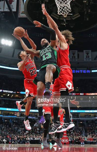 Marcus Morris of the Boston Celtics tries to get off a shot between Cameron Payne and Robin Lopez of the Chicago Bulls at United Center on December...