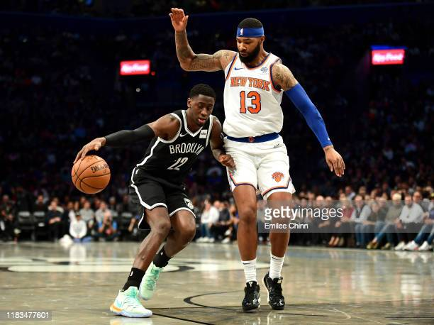 Marcus Morris Sr #13 of the New York Knicks guards Caris LeVert of the Brooklyn Nets as he dribbles the ball during the first half of their game at...