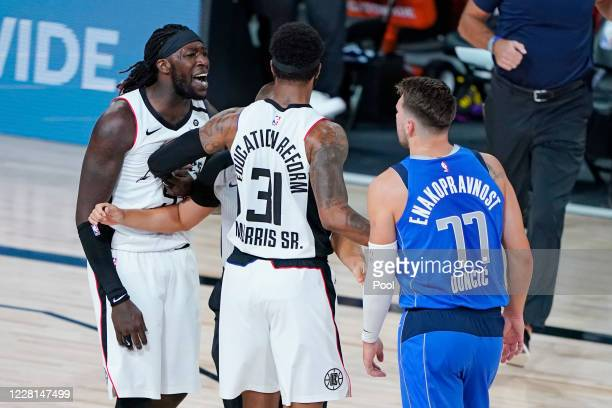 Marcus Morris Sr #31 of the LA Clippers gets between teammate Montrezl Harrell and Luka Doncic of the Dallas Mavericks during the first half of Game...