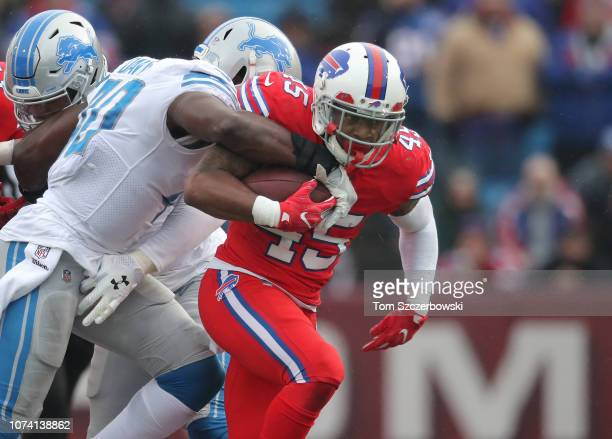 Marcus Murphy of the Buffalo Bills rushes for a first down in the first quarter during NFL game as Jarrad Davis of the Detroit Lions moves in to...
