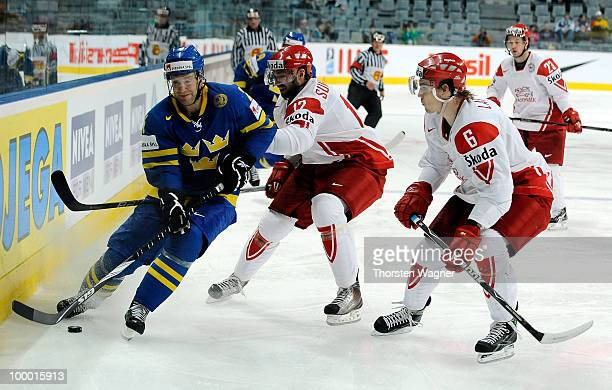 Marcus Nilson of Sweden battles for the puck with Alexander Sundberg and Stefan Lassen of Denmark during the IIHF World Championship quarter final...