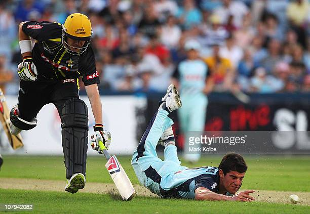 Marcus North of the Warriors streteches to make his ground as Moises Henriques of the Blues dives to attempt a run out during the Twenty20 Big Bash...