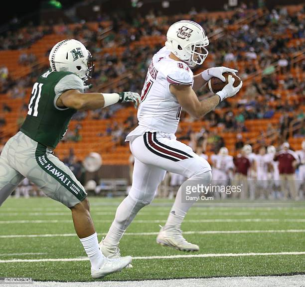 Marcus Odiah of the Massachusetts Minutemen makes the reception ahead of Damien Packer of the Hawai'I Rainbow Warriors to score a touchdown during...
