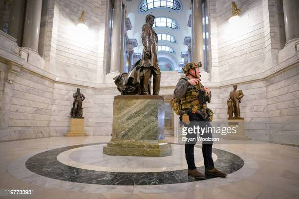 Marcus Olmstead stands below a statue of President Abraham Lincoln in the rotunda of the State Capitol carrying a semiautomatic firearm on January 31...