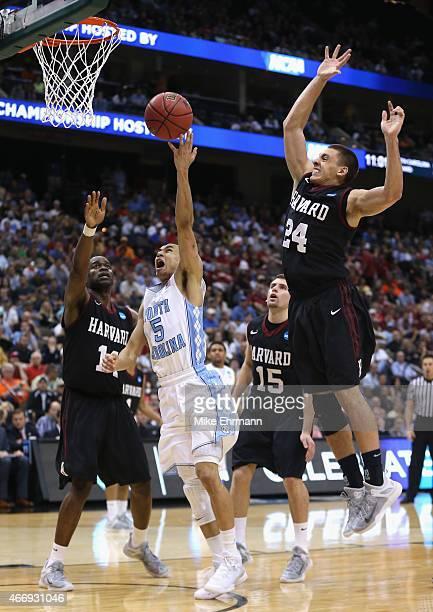 Marcus Paige of the North Carolina Tar Heels drives to the basket against teammates Steve Moundou-Missi and Jonah Travis of the Harvard Crimson...