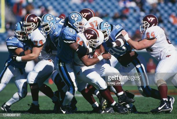 Marcus Parker, Running Back for the Virginia Tech Hokies is tackled by Brian Simmons and Vonnie Holliday of the University of North Carolina Tar...