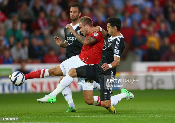Marcus Pedersen of Barnsley is tackled by Jose Fonte of Southampton during the Capital One Cup Second Round match between Barnsley and Southampton at...