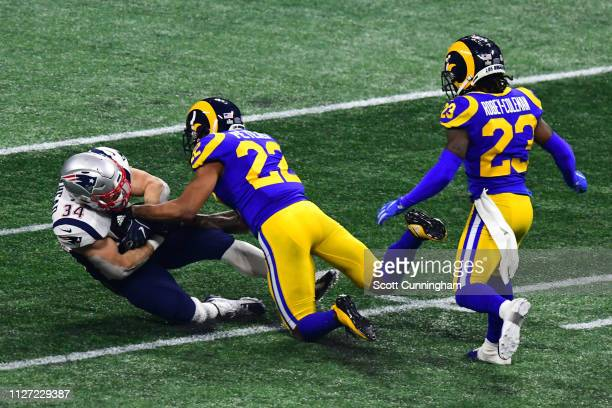 Marcus Peters and Nickell RobeyColeman of the Los Angeles Rams tackle Rex Burkhead of the New England Patriots in the second half during Super Bowl...