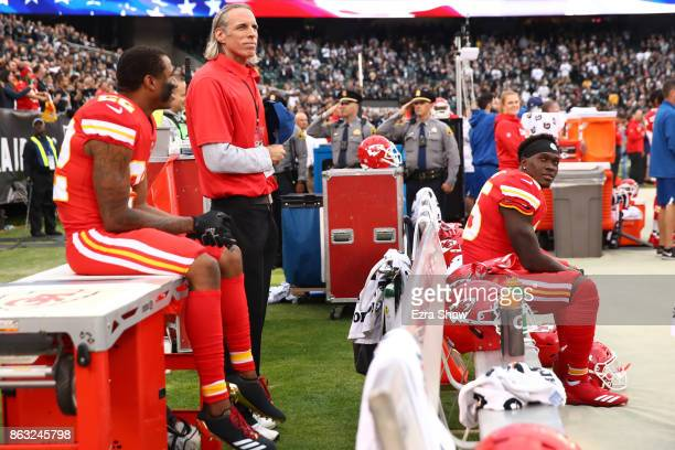 Marcus Peters and Ukeme Eligwe of the Kansas City Chiefs sit on the bench during the national anthem prior to their NFL game against the Oakland...