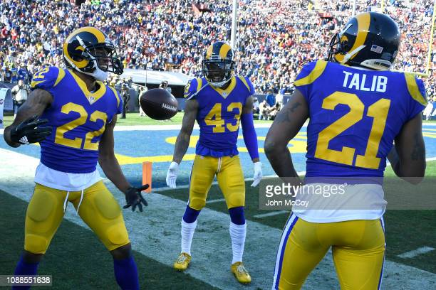 Marcus Peters celebrates intercepting the ball with John Johnson and Aqib Talib of the Los Angeles Rams against the San Francisco 49ers at Los...