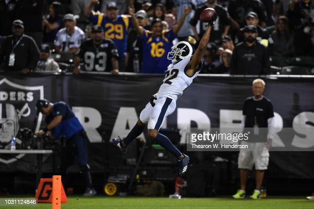 Marcus Peters of the Los Angeles Rams dives into the endzone after an interception of Derek Carr of the Oakland Raiders in the fourth quarter of...