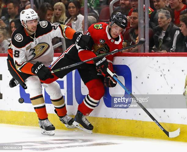 Marcus Pettersson of the Anaheim Ducks check Jonathan Toews of the Chicago Blackhawks into the boards at the United Center on October23 2018 in...